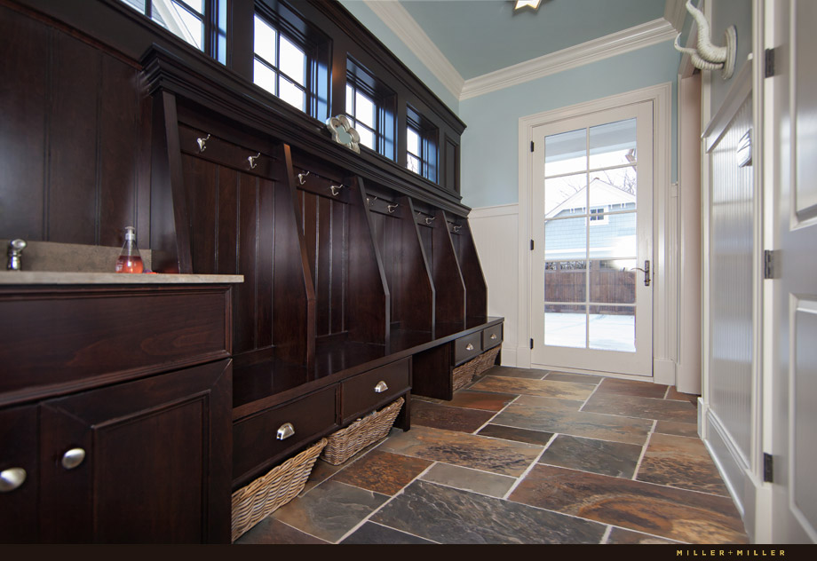mud room custom built in hooks drawers dark wood slate floor blue walls